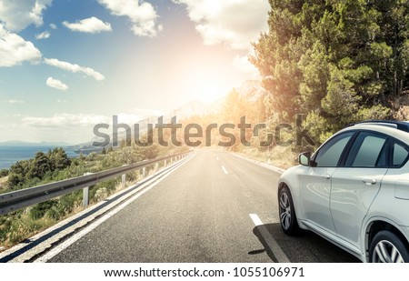 White car rushing along a high-speed highway. Toned photo. #1055106971