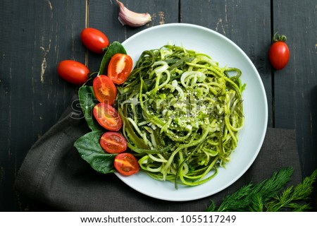 Zucchini raw vegan pasta with avocado dip sauce, spinach leaves and cherry tomatoes on plate. On dark background. Vegetarian healthy food #1055117249