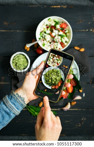 Woman hands takes photography of food on table with phone. Dinner or lunch. Zucchini raw vegan pasta with avocado dip suace. Smartphone photo for social networks post. Vegetarian, healthy, organic