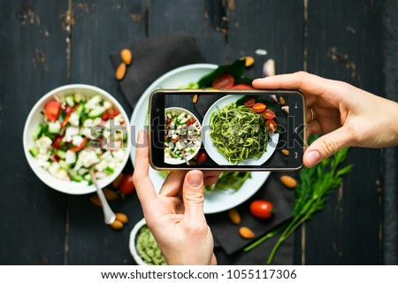 Woman hands takes photography of food on table with phone. Dinner or lunch. Zucchini raw vegan pasta with avocado dip suace. Smartphone photo for social networks post. Vegetarian, vegan, healthy