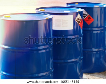 the close-up shot of blue color hazardous dangerous chemical drum barrels ,have warning labels of corrosive & flammable liquid in daylight on daytime. #1055145155