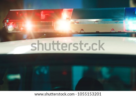 Police light and siren on the car in action. Siren on police car flashing, close-up. Emergency flashing police siren. Signal flasher isolated. Red siren flasher on the police car at night.