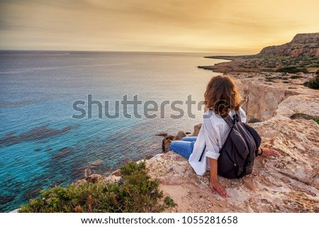 A stylish young woman traveler watches a beautiful sunset on the rocks on the beach, Cyprus, Cape Greco, a popular destination for summer travel in Europe #1055281658