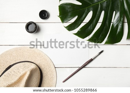 Art hipster flatlay with hat, monstera leaf, paper mockup, calligraphy nibs and ink. Working space surface top view with copy space. Creative work table for artist #1055289866
