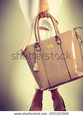 Fashion concept. Clothing and accessories. Woman hands holding beige handbag. Lady in white clothing with lacquered leather bag. #1055323460
