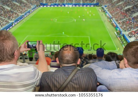 Three men are sitting in the stadium during a football match.
