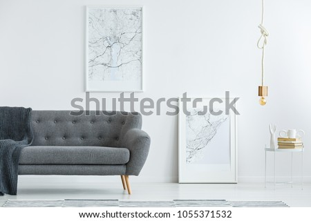 Elegant, gray sofa with wooden legs and large map posters on a white wall in a designer minimalist living room interior of an architect #1055371532