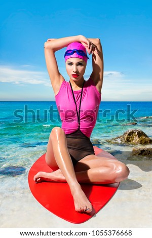 Pretty girl in a pink t-shirt sits on a red surfboard on the background seascape #1055376668