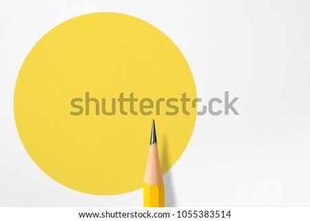 Minimalist template with copy space by top view close up macro photo of wooden yellow pencil isolated on white paper and combine with yellow circle shape. Flash light made smooth shadow from pencil. #1055383514