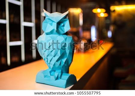 Blue paper owl on dark bar background. Origami toy. Origami bird. #1055507795