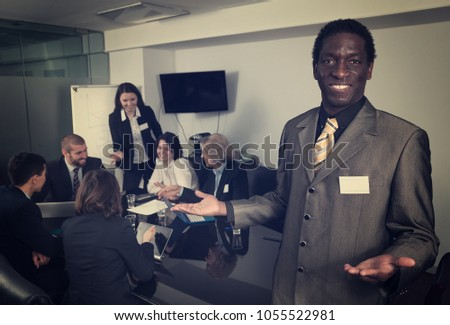 Portrait of smiling African American businessman with working team behind in conference room #1055522981