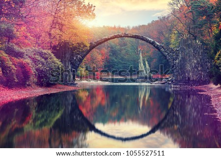 Awesome Autumn Landscape. Amazing sunset in Azalea and Rhododendron Park Kromlau. Rakotz Bridge, Rakotzbrucke Devil's Bridge in Kromlau, Saxony, Germany. Creative Artistic image. Picturesque Nature #1055527511