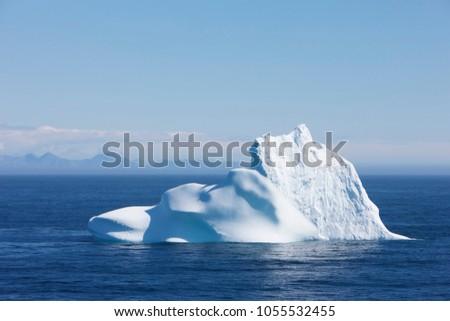 Greenland floating iceberg in deep blue ocean water. Global warming concept objet #1055532455
