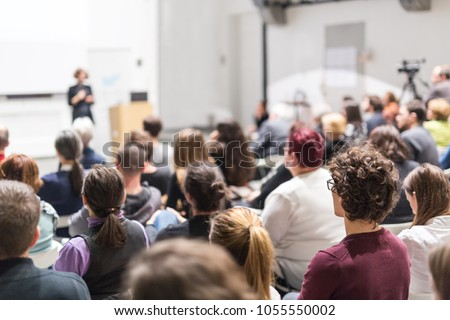 Female speaker giving presentation in lecture hall at university workshop. Audience in conference hall. Rear view of unrecognized participant in audience. Scientific conference event. Royalty-Free Stock Photo #1055550002