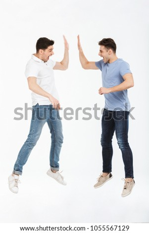 Full length portrait of two happy young men giving high five isolated over white background #1055567129