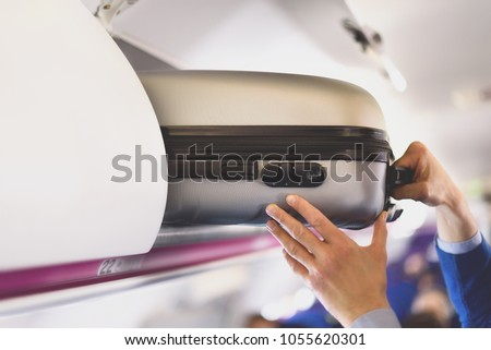 Hand-luggage compartment with suitcases in airplane. Hands take off hand luggage. Passenger put cabin bag cabin on the top shelf. Travel concept with copy space #1055620301