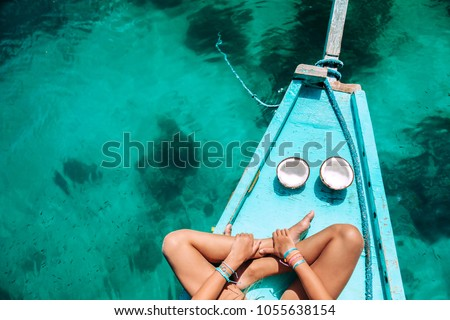 Young girl relaxing on the boat and eating coconut over clear sea water, top view. Travelling tour in Asia: El Nido, Palawan, Philippines. #1055638154
