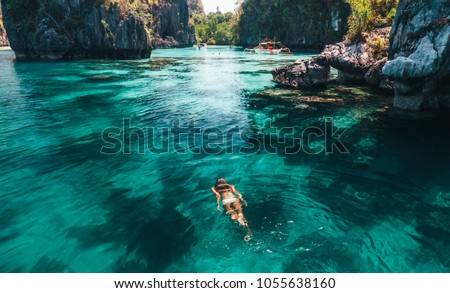 Young woman swimming in clear sea water in lagoon and looking at beautiful landscape. Travelling tour in Asia: El Nido, Palawan, Philippines. #1055638160