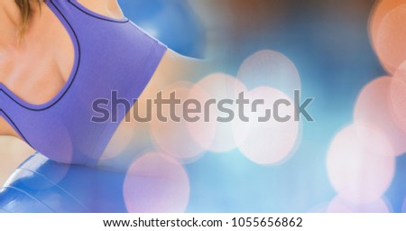 Digital composite of Woman mid section in sports bra with blue orange bokeh transition #1055656862