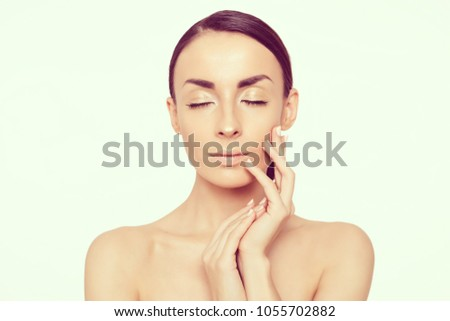 Tender Beauty Face. Portrait of a beautiful young smiling woman with fresh and clean skin on a white background. Skin care. Cosmetology. Women Health #1055702882