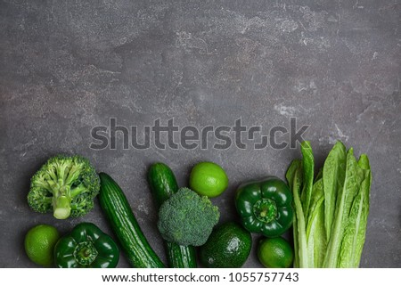 Different green vegetables and fruits on dark background, top view #1055757743