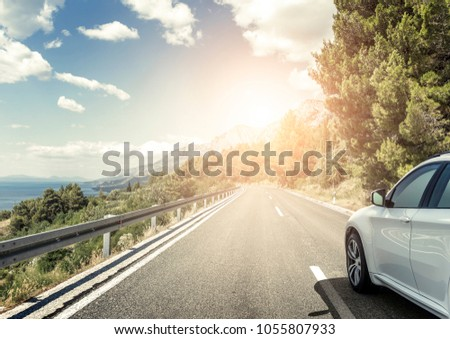 White car rushing along a high-speed highway. Toned photo. #1055807933
