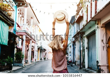 Boho girl walking on the city street. Travelling in Phuket Old Town in Thailand. #1055816447
