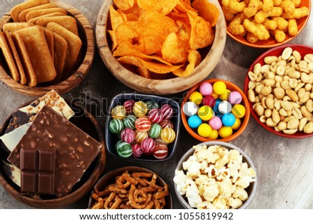 Salty snacks. Pretzels, chips, crackers in wooden bowls. Unhealthy products. food bad for figure, skin, heart and teeth. Assortment of fast carbohydrates food.  Royalty-Free Stock Photo #1055819942