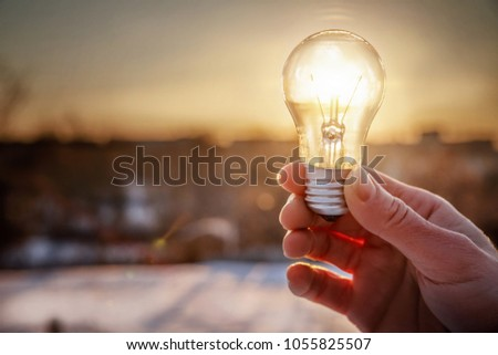 Light bulb in hand on the rising sun background. #1055825507