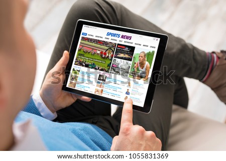 Man reading sports news on tablet. All contents are made up.