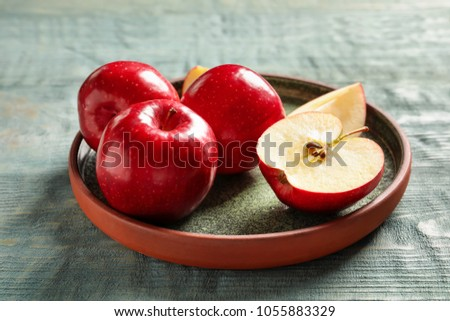 Plate with fresh ripe red apples on wooden background #1055883329