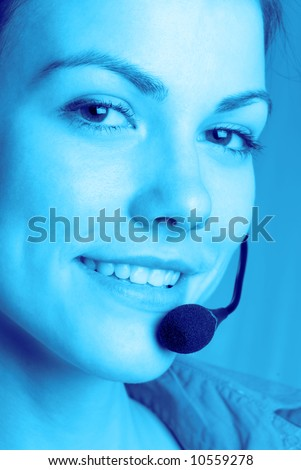 Beautiful young  representative of  client with headphones and  microphone smiles #10559278