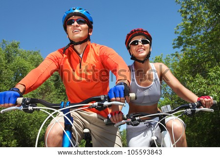 Young smiling couple cycling through summer park #105593843