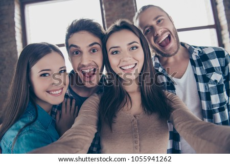 Let's take a picture! One two three smile! Close up portrait of carefree cheerful restless joyful funny people taking a picture on modern smartphone