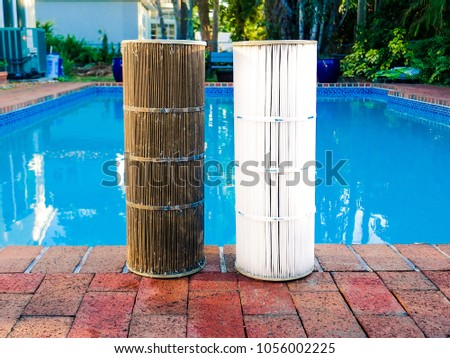 Juxtaposition of a dirty reusable washable pleated reinforced polyester cartridge pool filter next to a clean filter, after routine maintenance cleaning. Pool surrounded by bricks in background. #1056002225