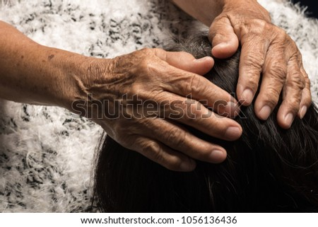 Old woman's hand Embracing the head of a daughter #1056136436