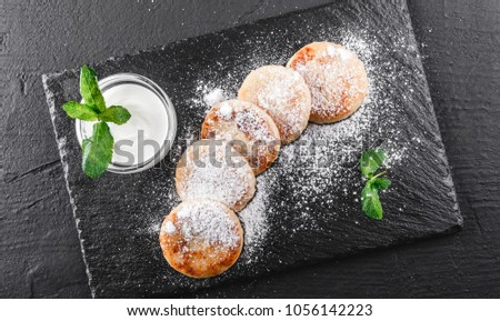 Frying homemade cottage cheese pancakes syrniki with powdered sugar, sour cream. View on a dark grey stone surface. Healthy breakfast. Top view #1056142223