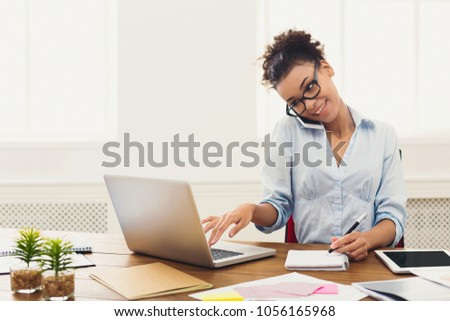 Happy african-american business woman talking on mobile at office. Young female manager consulting on phone, using laptop at working place, copy space #1056165968