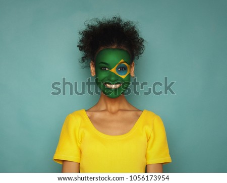 Portrait of a woman with the flag of Brazil painted on her face. Football or soccer team fan, sport event, faceart and patriotism concept. Studio shot at blue background, copy space #1056173954