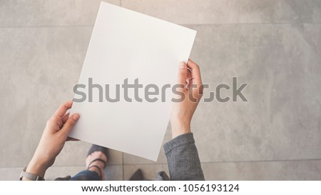 Person holding white empty paper Royalty-Free Stock Photo #1056193124