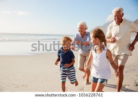 Grandparents Running Along Beach With Grandchildren On Summer Vacation #1056228761