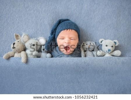 Newborn baby boy yawning and lying between plush toys Royalty-Free Stock Photo #1056232421