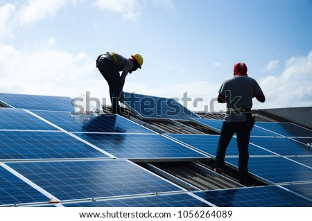 Installing a Solar Cell on a Roof Royalty-Free Stock Photo #1056264089
