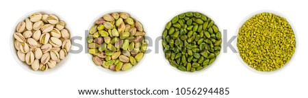 Pistachios in white porcelain bowls. Roasted pistachio seeds in shells and shelled. Green, dried fruits, whole and chopped. Pistacia vera. Isolated food photo close up from above on white background. #1056294485
