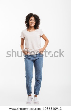 Full length photo of vivacious american woman wearing jeans and t-shirt posing on camera with candid smile and hands in pocket isolated over white background #1056310913