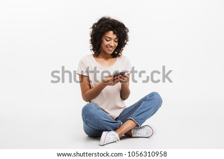 Portrait of happy young afro american woman using mobile phone while sitting on a floor with legs crossed isolated over white background #1056310958