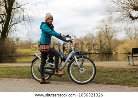 A young woman with a bicycle in the park #1056321326