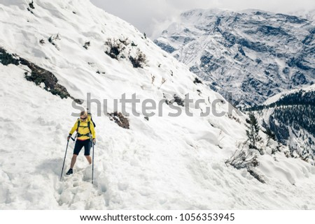 Woman hiker trekking in Himalaya Mountains in Nepal. Hiking on snow white in winter nature, high mountains in Asia, beautiful inspirational landscape. #1056353945