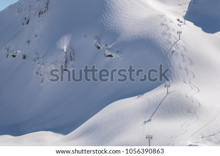 Skiers or snowboarders with skis on his shoulder and off-piste slope with traces of skis, snowboards. Beautiful background with mountains, freeride, people and path upstairs. #1056390863