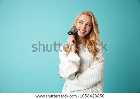 Portrait of a lovely young blonde woman in sweater showing credit card and looking away at copy space isolated over blue background #1056423650